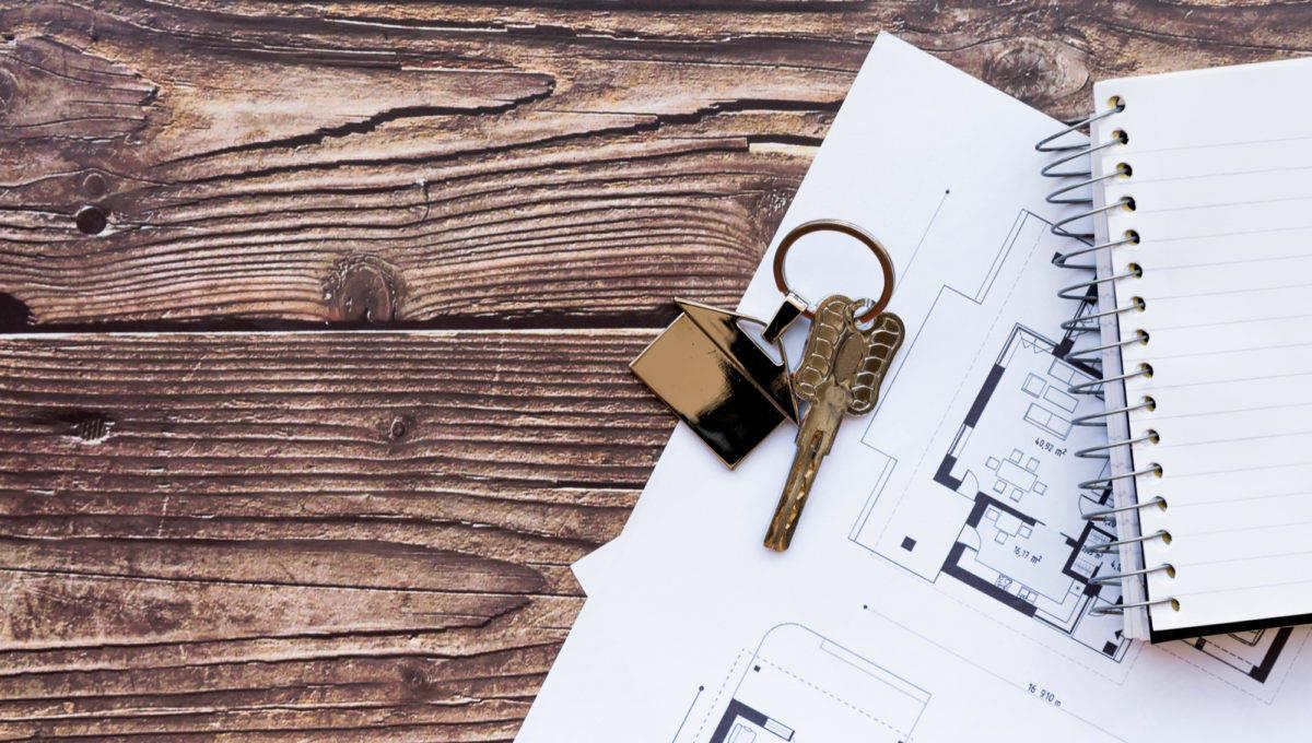 close-up-house-keys-blueprint-new-home-spiral-notebook-wooden-textured-backdrop